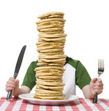 Pile of Pancakes. Little boy hidden behind  a giant plate of pancakes, with a knife and fork visible on a table cloth Royalty Free Stock Photo
