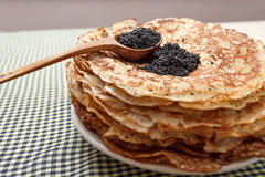 Pile of pancakes with black caviar on top on white plate Royalty Free Stock Images