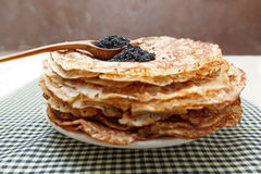 Pile of pancakes with black caviar on top on white plate Stock Photography