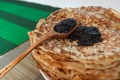 Pile of pancakes with black caviar on top on white plate Royalty Free Stock Image