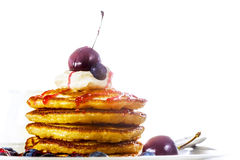 Pile of pancakes with blueberries, cherries and sour cream Royalty Free Stock Image