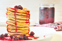 Pile of Pancakes with cherry jam in white  plate on the  table Royalty Free Stock Image