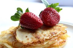 Pile of pancakes with juicy strawberries on white plate stock photo