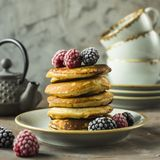 Pancakes with raspberries and blackberries. A pile of pancakes on a plate with raspberries and blackberries next to cups and a kettle on a gray table. Summer Royalty Free Stock Photography