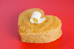 Pile of pancakes in the shape of a heart on red with flake of bu Royalty Free Stock Photos