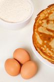 Pile of pancakes with some flour and eggs Royalty Free Stock Photography