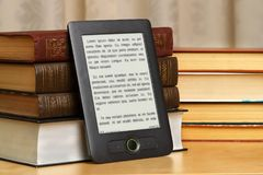 Pile of paper books with e-book. Royalty Free Stock Photo