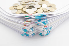 Pile of paperwork with colorful paperclip have stack gold coins. Step pile of paperwork with colorful paperclip have stack of gold coins on a white background Stock Photo