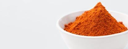 Pile of paprika powder in white bowl royalty free stock image