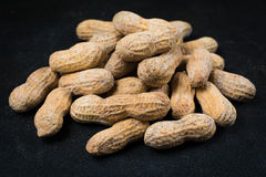 Pile of Peanuts in Shells on a Black Surface Royalty Free Stock Image