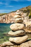 Pile of pebbles on the sea front on a beautiful day. Pebble stack on the seashore. Stone pyramid. Balanced Zen stones. Pile of pebbles on the sea front on a royalty free stock image