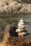 Pile of pebbles on the sea front on a beautiful day. Pebble stack on the seashore. Stone pyramid. Balanced Zen stones. Pile of pebbles on the sea front on a stock photography