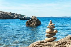 Pile of pebbles on the sea front on a beautiful day. Pebble stack on the seashore. Stone pyramid. Balanced Zen stones. Pile of pebbles on the sea front on a stock photos