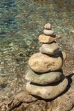 Pile of pebbles on the sea front on a beautiful day. Pebble stack on the seashore. Stone pyramid. Balanced Zen stones. Pile of pebbles on the sea front on a stock images