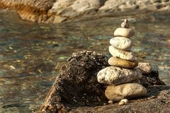 Pile of pebbles on the sea front on a beautiful day. Pebble stack on the seashore. Stone pyramid. Balanced Zen stones. Pile of pebbles on the sea front on a royalty free stock photo