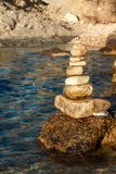 Pile of pebbles on the sea front on a beautiful day. Pebble stack on the seashore. Stone pyramid. Balanced Zen stones. Pile of pebbles on the sea front on a royalty free stock photos