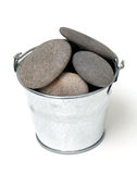 Pile of pebles in a metal bucket Stock Images