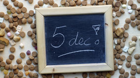 Pile of pepernoten. 5th december in Dutch written on a chalkboard between ginger nuts and candy's for the Dutch Santa-Claus celebration of the 5th of December Royalty Free Stock Photo