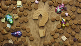 Pile of pepernoten. Wooden question mark between ginger nuts and candy's for the Dutch Santa-Claus celebration of the 5th of December Royalty Free Stock Photography