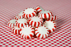 Striped hard candy peppermints. Close up of hard candy peppermints on red and white gingham royalty free stock photography