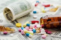 Pile of pharmaceutical drug and medicine pills on dollar money, cost of healthcare and medical insurance Royalty Free Stock Images