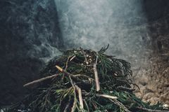 a pile of pine branch smoking on the holy sacred fire with a ray of sun peaking in from the top stock images