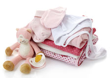 Pile of pink baby clothes. Pacifier and toy isolated on white background stock photos