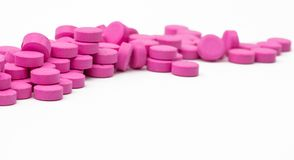 Pile of pink tablets pills isolated on white background with clipping path. Royalty Free Stock Photo