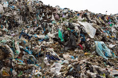 Pile of plastic bags and other refined petroleum products dumped in landfill. Garbage heap gives infiltrate into ground Royalty Free Stock Photo