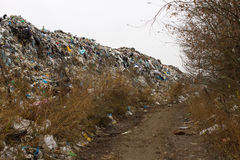 Pile of plastic bags and other refined petroleum products dumped in landfill. Garbage heap gives infiltrate into ground. Waste sor Royalty Free Stock Image