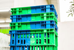 Pile of Plastic Pallets Blue And Gray Color Stacked Beside A Store. Stock Photos