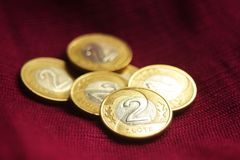 A pile of Polish two zloty coins on royal red-purple background. stock photo