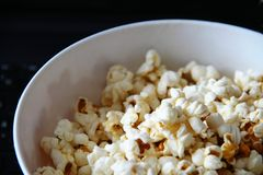 Top view of a pile of popcorn caramel popcorn in a plate on a glass table royalty free stock photography