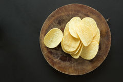 Pile of potato chips on cutting board Royalty Free Stock Image