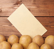 Pile of potatoes against piece of paper Stock Photo
