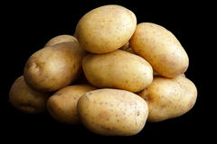 Pile of potatoes arranged on black Stock Images