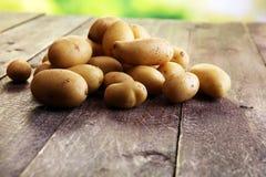 Pile of potatoes lying on wooden boards. Fresh potato.  Stock Photo