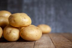 Pile of potatoes on old wooden table. royalty free stock photo