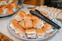 A pile of prepared turkey sandwiches stacked on a plate with tongs for serving. royalty free stock image