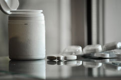 Pile of prescription pills with pill bottle in the background Stock Photos