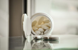 Pile of prescription pills with pill bottle in the background Royalty Free Stock Image