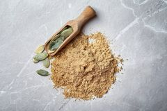 Pile of pumpkin flour and scoop with seeds. On gray background Stock Photography
