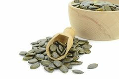 A pile of pumpkin seeds with wooden scoop Royalty Free Stock Photography