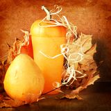 Pile of pumpkins with autumn foliage on background Royalty Free Stock Image