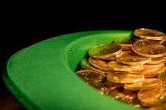 Pile of pure gold coins inside green hat St Patricks Day. Treasure of pure gold eagle coins inside the rim of a green velvet hat to celebrate luck on St Patrick` Stock Image