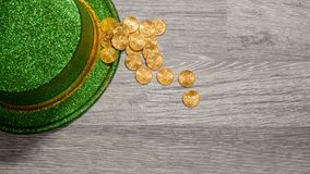 Pile of pure gold coins inside rim of green hat St Patricks Day. Treasure of pure gold eagle coins inside the rim of a green velvet hat to celebrate luck on St Royalty Free Stock Image