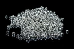 A pile of pure silver granules. Isolated on dark background. Selective focus stock images