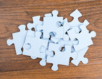 Pile of puzzle pieces on table. Stock Images