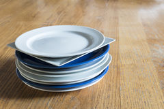 Pile of random white and blue plates on a wooden table Stock Images