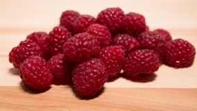 Pile of raspberries on a natural wooden background. royalty free stock photography